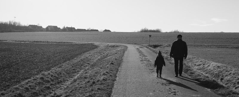 Grandfather walking with grandson on a farm
