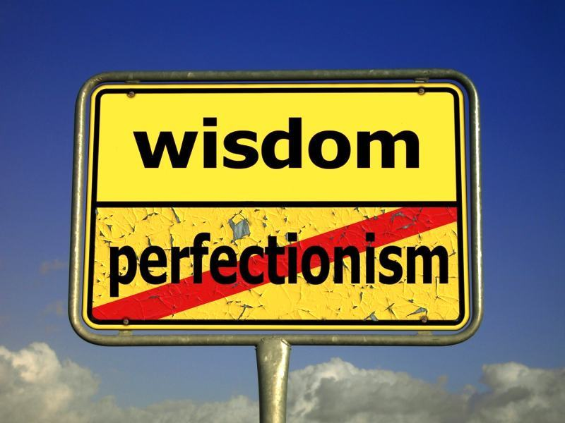 Sign that reads 'wisdom', with perfectionism crossed out underneath