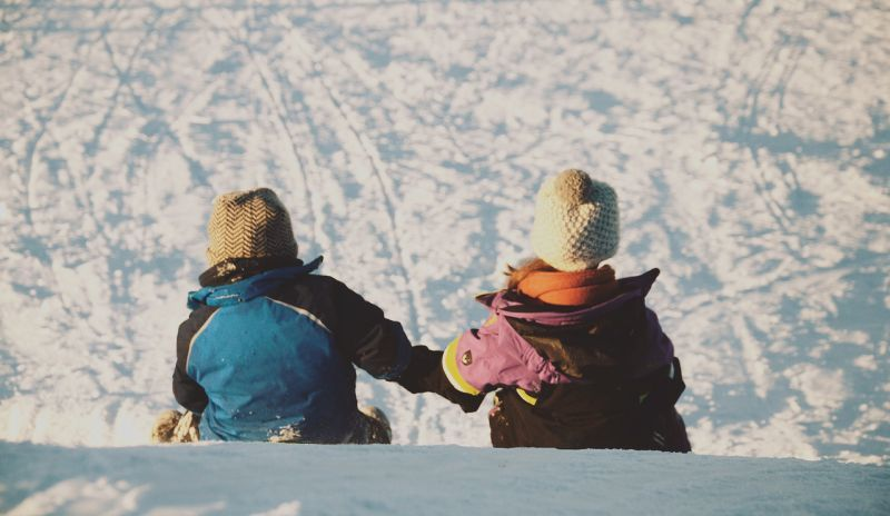 Two kids sitting on a hill holding hands in winter
