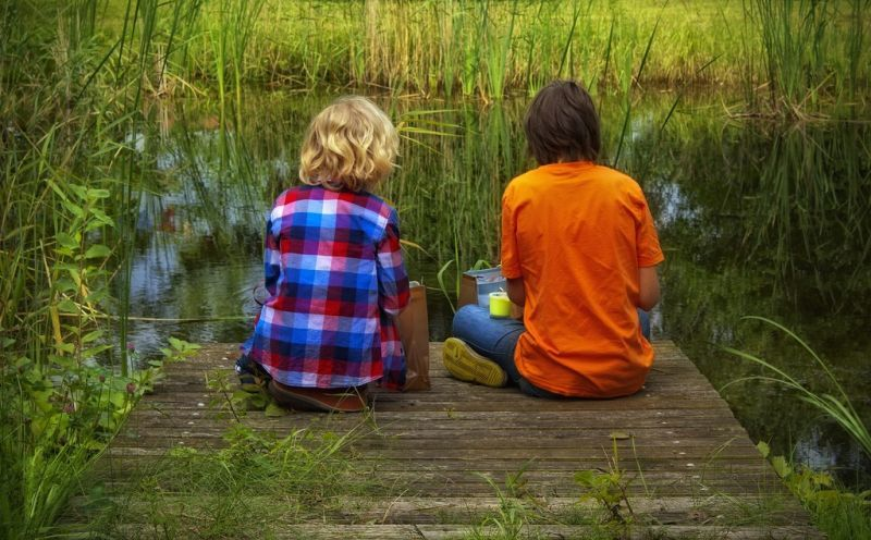Two friends sitting on dock by long grass