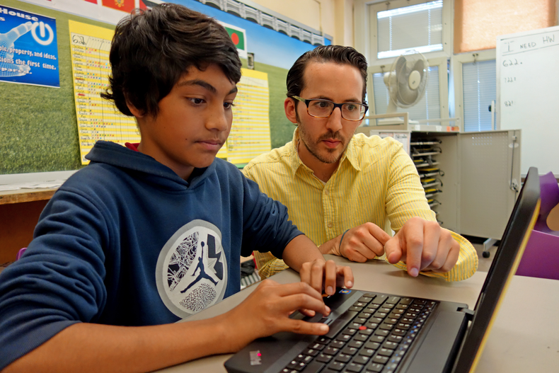 Teacher Aaron Kaswell works with seventh grader Mohammed in the *Teach to One: Math* model, a personalized instruction model developed by New Classrooms.
