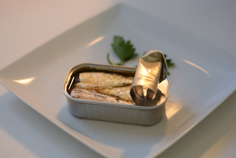 Open can of sardines on a plate