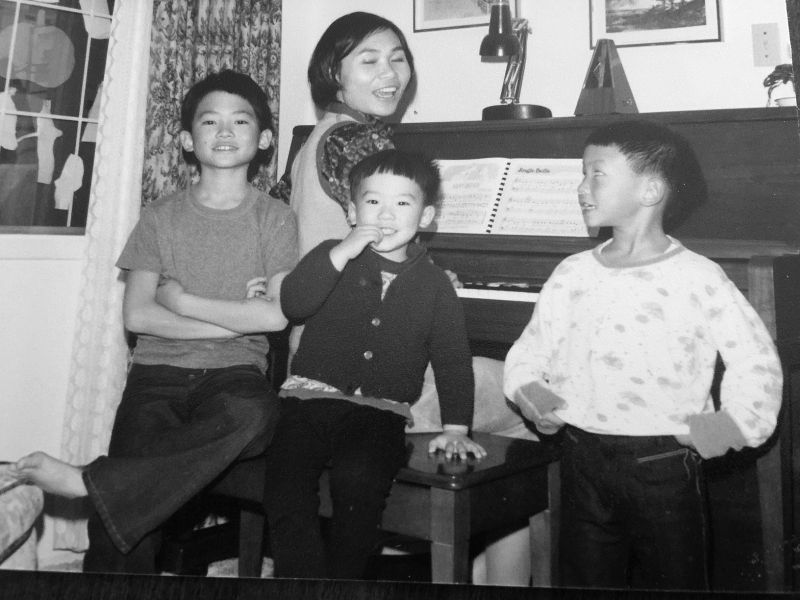 Mom playing piano with sons