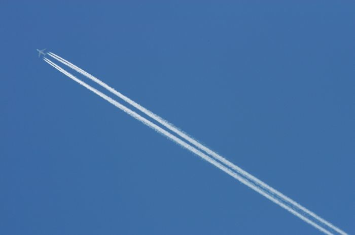 Jet streaking across sky leaving contrails