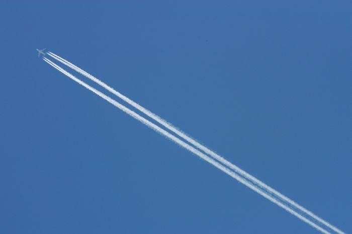 Jet streaking across sky leaving contrails