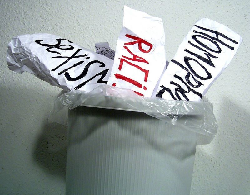 Crumpled papers in garbage that say: sexism, racism, homophobia